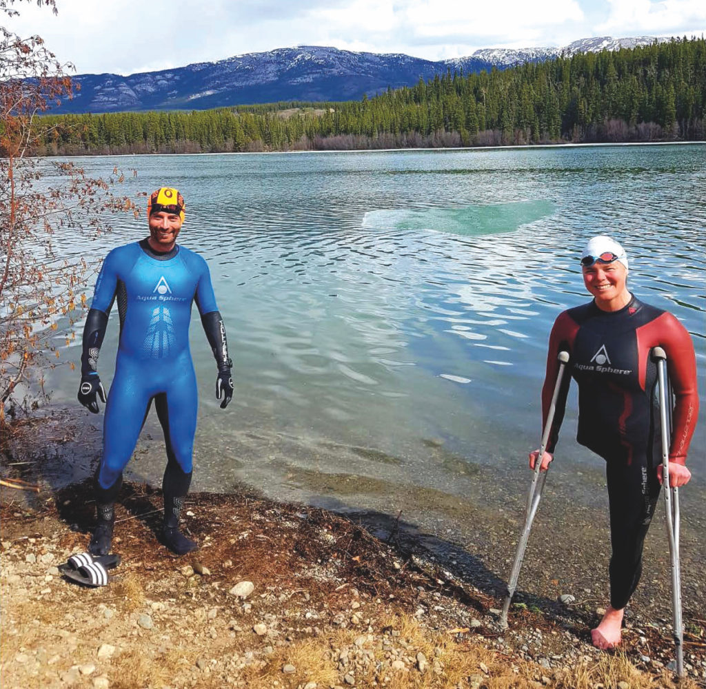 Picture of Stephanie Dixon and another swimmer in swim gear standing at the edge of a lake.