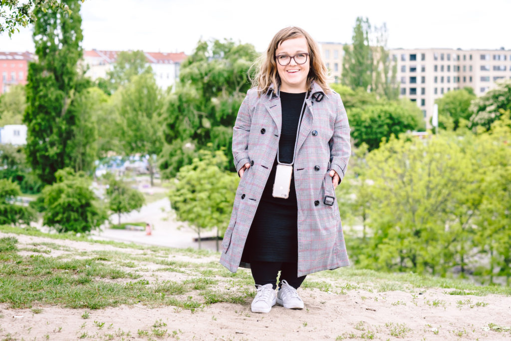 A fashionable woman with dwarfism standing outside and smiling.