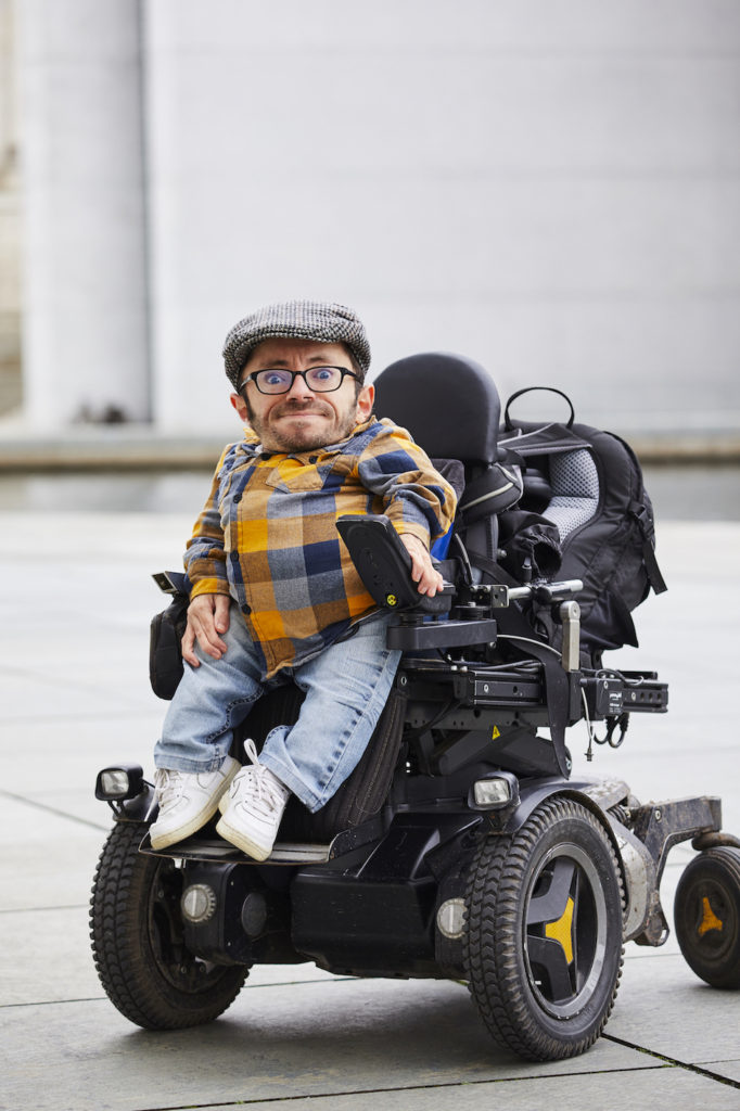A fashionable young man with dwarfism sitting in a mobility aid.