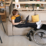 Young woman sitting on couch with her feet resting on her wheelchair.