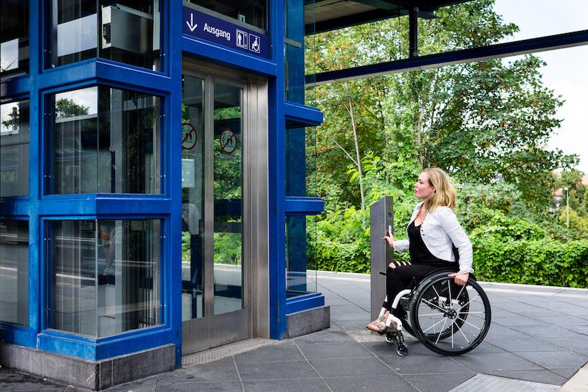 A woman in a wheelchair pushing an elevator button.