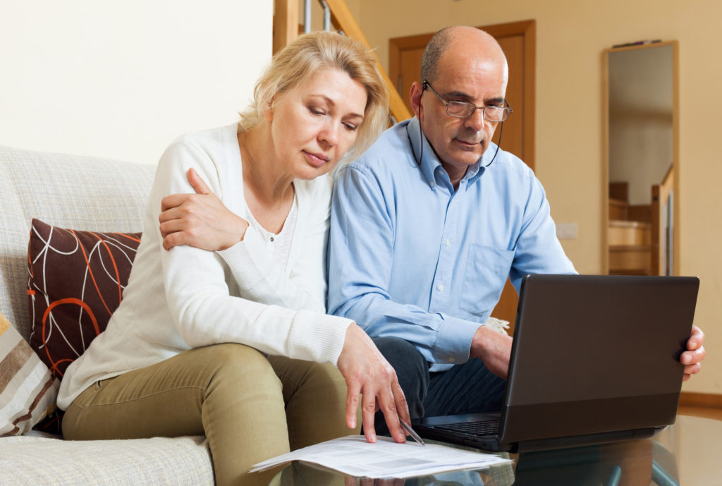 A picture of a middle-aged couple. The man is looking at a laptop and the woman is looking at papers.