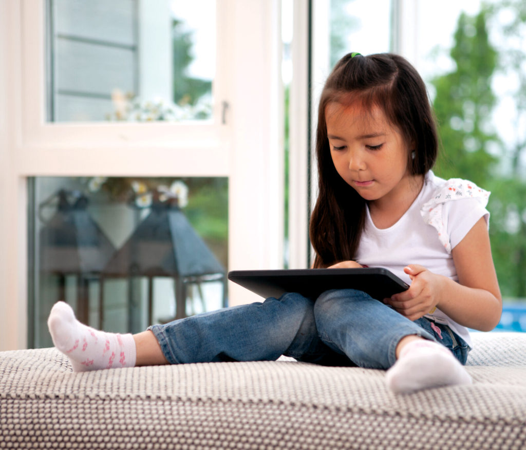 A young girl using a tablet or ipad.