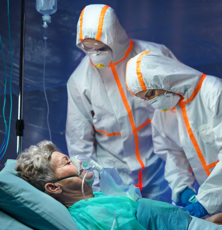 Two doctors in full PPE standing at an older female patient's bedside.