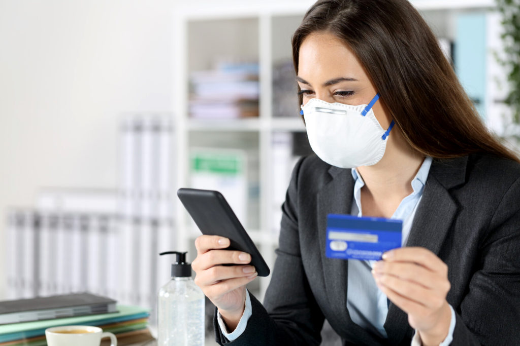 A business woman wearing a mask looking at her phone while holding her credit card.