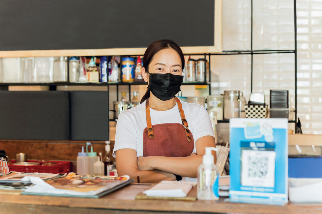 An Asian woman wearing a mask standing behind a cafe counter.