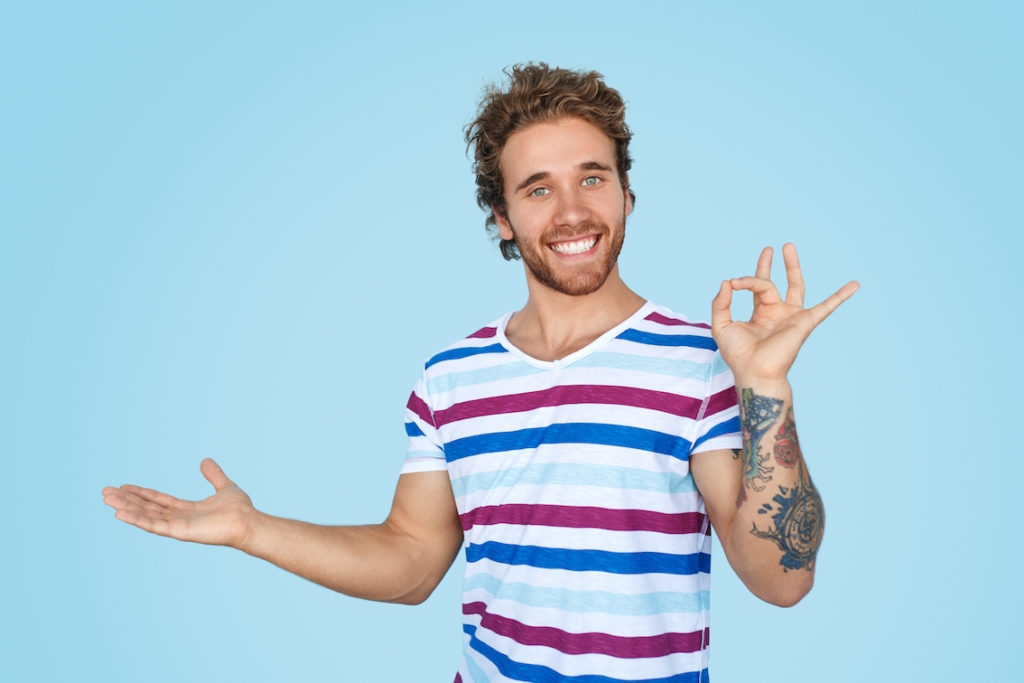 """Man with a huge smile holding one arm out to his side and the other hand making the """"okay"""" sign."""