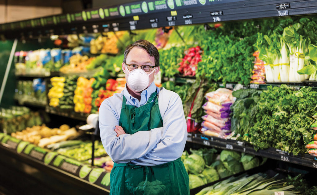 A male grocery store worker wearing a mask and standing in front of vegetables.