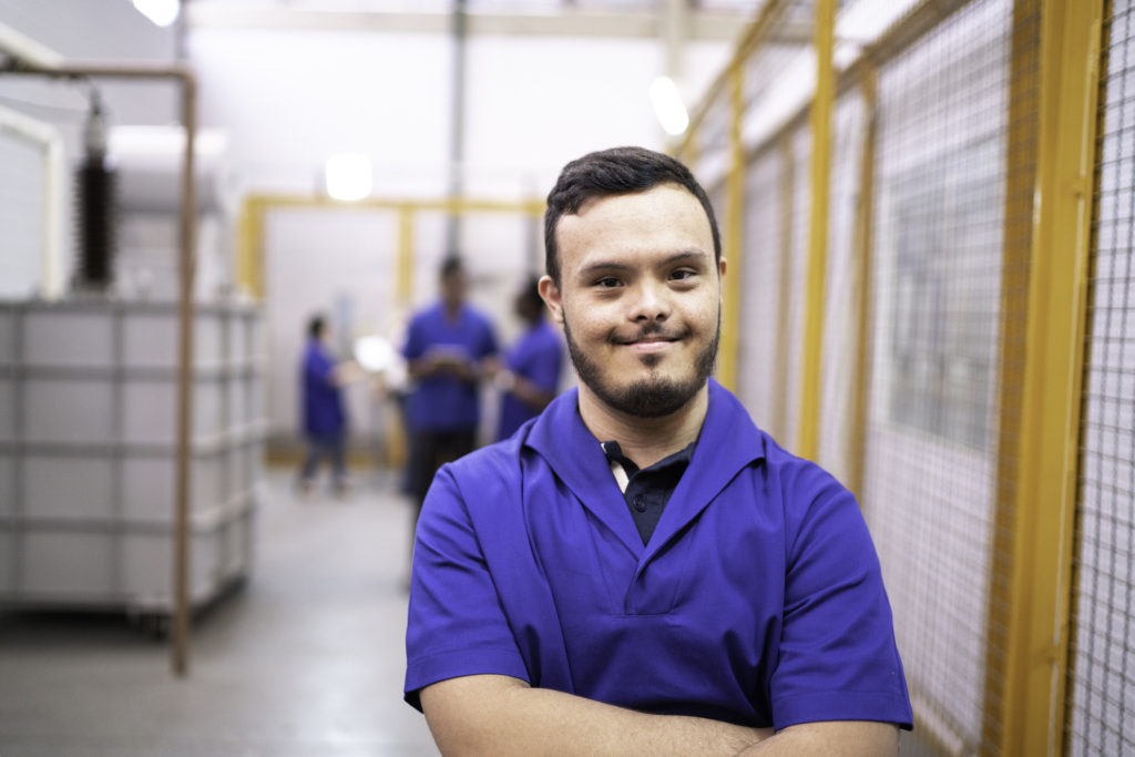 A man with down syndrome smiling at work.