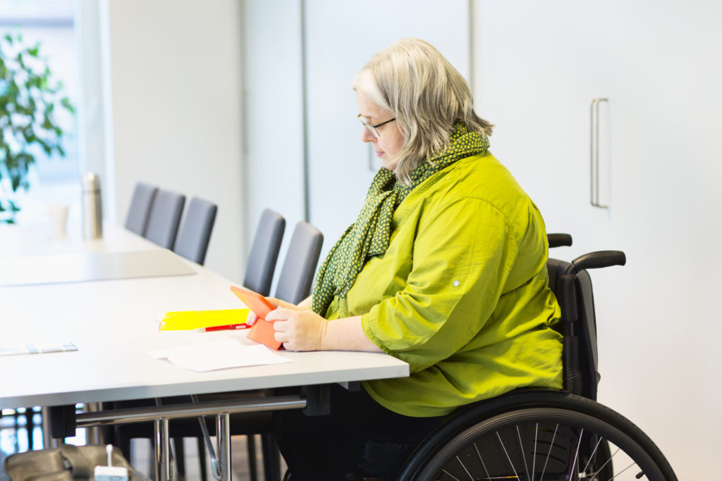 A woman in a wheelchair sitting at a conference table.